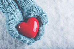 Woman hands in light teal knitted mittens are holding beautiful glossy red heart in snow background. Love, St. Valentine concept