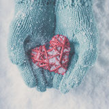 Woman hands in light teal knitted mittens are holding beautiful glossy red heart on snow background. Love, St. Valentine concept Stock Photo