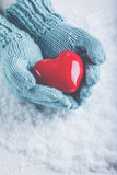 Woman hands in light teal knitted mittens are holding beautiful glossy red heart in snow background. Love, St. Valentine concept Stock Images