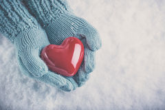 Woman hands in light teal knitted mittens are holding beautiful glossy red heart on snow background. Love, St. Valentine concept Stock Photos