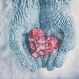 Woman hands in light teal knitted mittens are holding beautiful glossy red heart on snow background. Love, St. Valentine concept Stock Photography