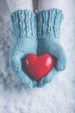 Woman hands in light teal knitted mittens are holding beautiful glossy red heart in snow background. Love, St. Valentine concept Royalty Free Stock Images