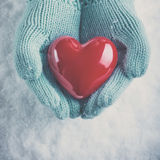 Woman hands in light teal knitted mittens are holding beautiful glossy red heart on snow background. Love, St. Valentine concept Royalty Free Stock Photo