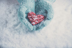 Woman hands in light teal knitted mittens are holding beautiful glossy red heart on snow background. Love, St. Valentine concept Stock Image
