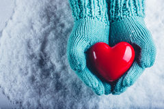 Woman hands in light teal knitted mittens are holding a beautiful glossy red heart in a snow background. St. Valentine concept. Royalty Free Stock Images