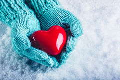 Woman hands in light teal knitted mittens are holding a beautiful glossy red heart in a snow background. St. Valentine concept. Royalty Free Stock Photo