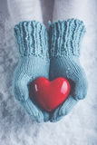 Woman hands in light teal knitted mittens are holding beautiful glossy red heart in snow background