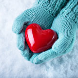 Woman hands in light teal knitted mittens are holding a beautiful glossy red heart in a snow. Love and St. Valentine concept. Royalty Free Stock Images