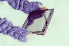 Woman hands in light teal knitted mittens are holding modern tab Stock Images