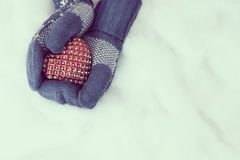 Woman hands in light teal knitted mittens are holding red heart Royalty Free Stock Images
