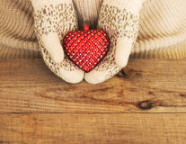 Woman hands in light teal knitted mittens are holding red heart. On wooden background. Winter, Valentines day and Christmas concept Royalty Free Stock Photography