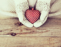 Woman hands in light teal knitted mittens are holding red heart Stock Photography