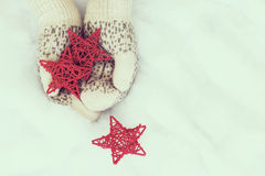 Woman hands in light teal knitted mittens are holding red stars Stock Image