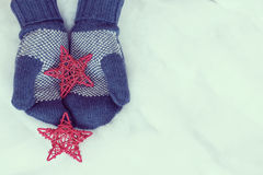 Woman hands in light teal knitted mittens are holding red stars Stock Photography