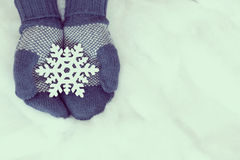Woman hands in light teal knitted mittens are holding snowflake Royalty Free Stock Images