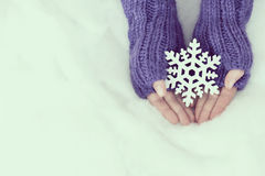 Woman hands in light teal knitted mittens are holding snowflake Stock Image