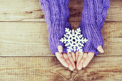 Woman hands in light teal knitted mittens are holding snowflake Royalty Free Stock Photos
