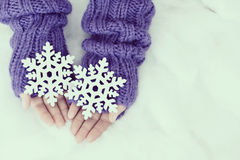 Woman hands in light teal knitted mittens are holding snowflakes Stock Image