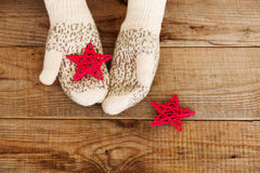 Woman hands in light teal knitted mittens are holding star on snow background. Royalty Free Stock Photos