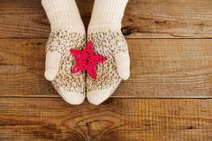 Woman hands in light teal knitted mittens are holding star on snow background. Stock Images