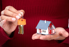 Woman Hands with little house and key. Royalty Free Stock Images