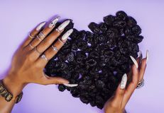 Woman hands with long nails manicure holding fruits in shape of. Heart on purple background close up stock photography