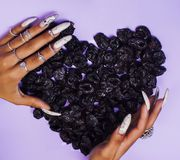 Woman hands with long nails manicure holding fruits in shape of heart. Closeup stock photo
