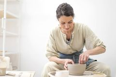 Woman hands makes clay pot on the pottery wheel stock photo