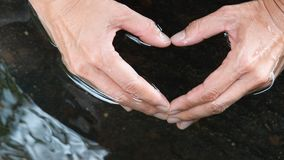 Woman hands making heart shape in clean and clear water. The concept of  water conservation and saving Royalty Free Stock Photography