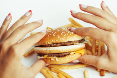 Woman hands with manicure holding hamburger and Royalty Free Stock Image