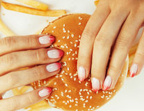 Woman hands with manicure holding hamburger and french fries isolated on white, food unhealthy Royalty Free Stock Images
