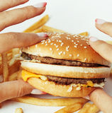 Woman hands with manicure holding hamburger and french fries isolated on white, food unhealthy Stock Images
