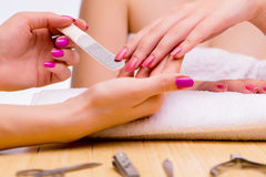 The woman hands during manicure procedure Stock Photos