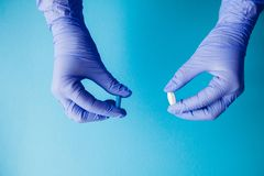 Woman hands in medical gloves giving two big pills. Blue and white. Make your selection stock image