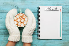 Woman hands in mittens hold cup of hot cocoa or chocolate with marshmallow and notebook with wish list on turquoise vintage table. Royalty Free Stock Photos