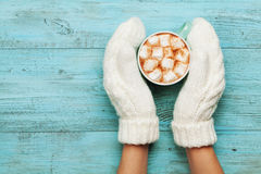 Woman hands in mittens hold cup of hot cocoa or chocolate with marshmallow on turquoise vintage table from above. Flat lay style. Royalty Free Stock Photos