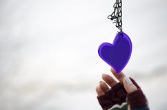 Woman hands in mittens reaching for a heart Royalty Free Stock Images