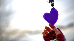 Woman hands in mittens reaching for a heart Royalty Free Stock Image