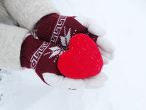 Woman hands in mittens with red heart on snow Stock Photos