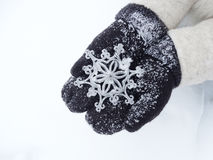Woman hands in mittens with snowflake decor on snow Royalty Free Stock Photos