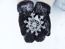 Woman hands in mittens with snowflake decor on snow Stock Photo