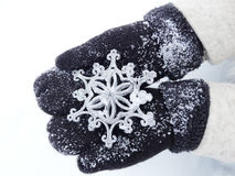Woman hands in mittens with snowflake decor on snow Stock Image