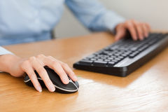 Woman with hands on mouse and keyboard Stock Photos