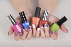 Woman hands with nail polishes and bright colorful manicure. Multi colored purple and white manicure with polish in hand Stock Image