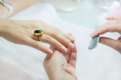 Woman hands in a nail salon receiving a manicure by a beautician Royalty Free Stock Photo