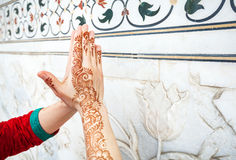 Woman hands in namaste in India. Woman in red Indian costume ding Namaste gesture by hand in henna paintings  near the marble wall with floral pattern in Taj Royalty Free Stock Photography
