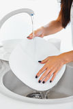 Woman hands with nice manicure washing dishes in the kitchen Royalty Free Stock Images