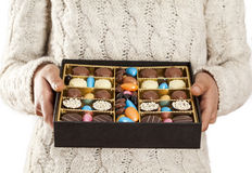 Woman hands offering chocolates in box royalty free stock photos