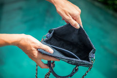 Woman hands opening empty luxury snakeskin python handbag on a swimming pool background royalty free stock image