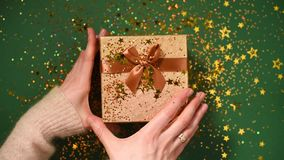 Woman hands opening gift box. Sparkling gold stars, glitter confetti over present. Unpacking gift on green background